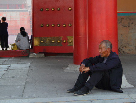 bejing: An old man sits at the doors to the Forbidden City in Beijing China