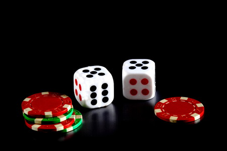 unpredictable: Dice and gambling chips on a black surface