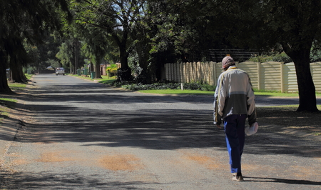 dejected: A poor and homeless man walks in an urban street