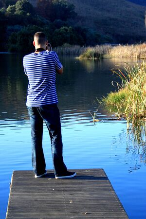 tog: A photographer works on a jetty Stock Photo