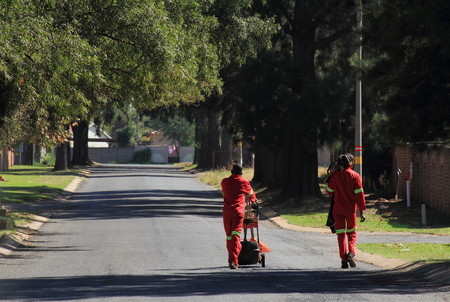 residential street: Red-cladcouncil workers walk on a residential street