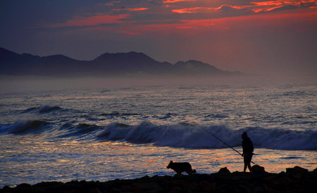 angler: An angler and his dog silhouetted against the early morning light