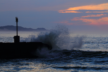 breakwater: A wave crashes over a breakwater