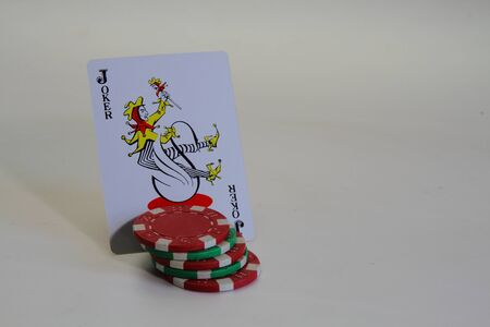 joker playing card: A joker playing card and casino chips Editorial