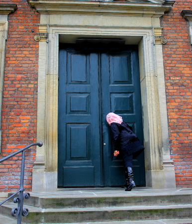 prying: A woman peeps through the keyhole of a green wooden door