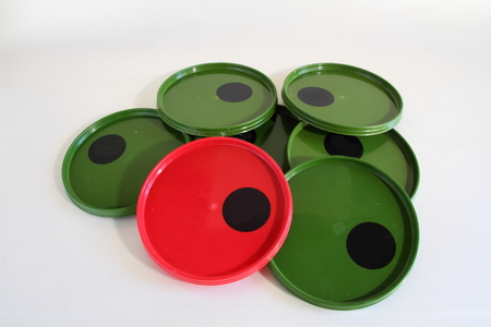 'odd one out': Green plastic lids and one red lid