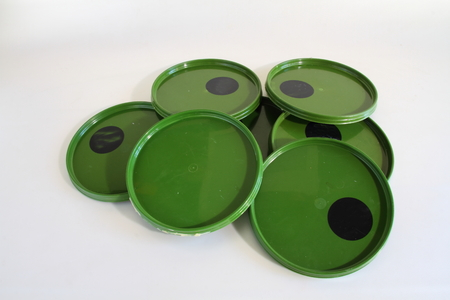 'odd one out': Green plastic lids with an odd one out