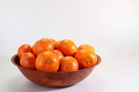 clementines: Fresh clementines in a wooden bowl on a white background