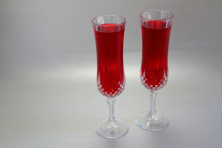 landscape format: Two glasses of red juice on white background in landscape format