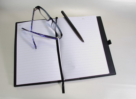 shorthand: A blank paged notebook with glasses and a pen