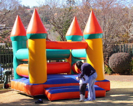 A mother, a child and a jumping castle Imagens