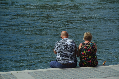 to ponder: A couple sits next to the river