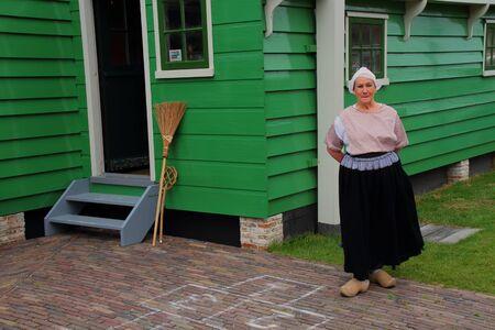 dutch: Traditional dutch woman outside a farmhouse Editorial