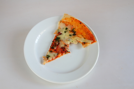 mouthful: Slice of pizza with bite missing on a white plate with white background Stock Photo