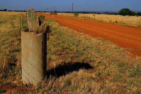 distance marker: A distance marker on a dusty dirt road