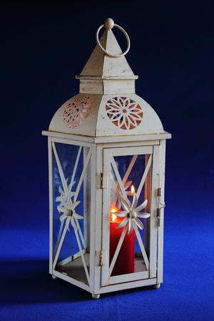 ble: White lantern with a red candle against a blue background Stock Photo
