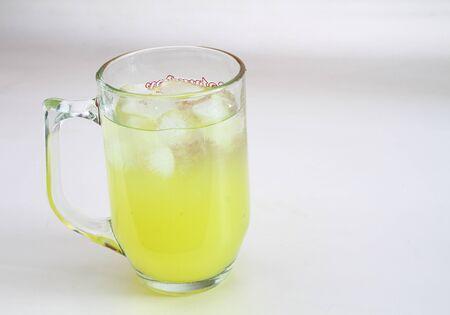 A mug of orange juice with ice