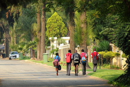 Black children walk home from school through a leafy predominantly white residential neighborhood in Gauteng province of post-apartheid South Africa