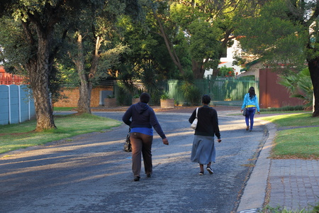 Black laborers walk to work through a residential suburp in post-apartheid South Africa as there is no public transport infrastructure