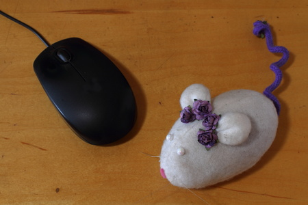A computer mouse and a toy mouse together on a wood surface Stock Photo