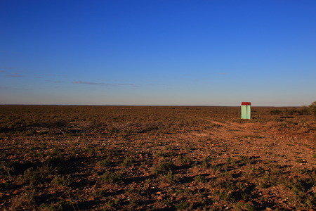 A small green corrugated iron building with a red roof on an open and deserted field with a clear blue sky Stock Photo