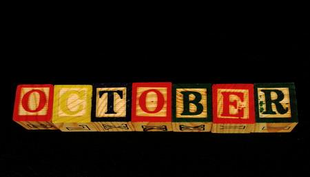 De term oktober visueel weergegeven op een zwarte achtergrond in liggend formaat met behulp van kleurrijke houten blokken Stockfoto - 77494535
