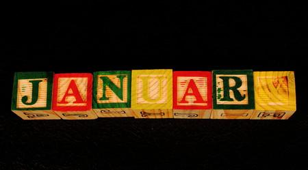De term januari visueel weergegeven op een zwarte achtergrond in liggend formaat met behulp van kleurrijke houten blokken Stockfoto - 77515680