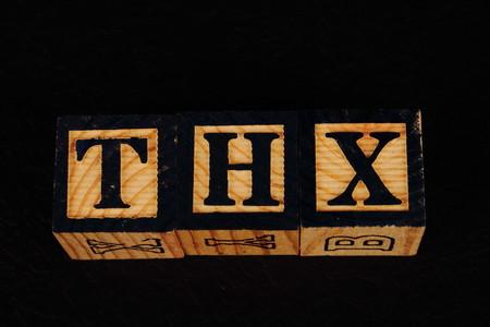 De term THX visueel weergegeven op een zwarte achtergrond in liggend formaat met behulp van kleurrijke houten blokken Stockfoto - 77517444