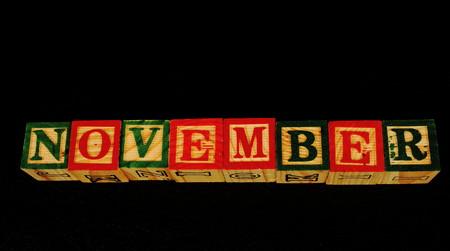 De term November visueel weergegeven op een zwarte achtergrond in liggend formaat met behulp van kleurrijke houten blokken Stockfoto - 77651571