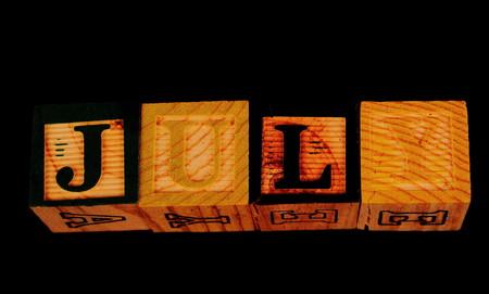 De term juli visueel weergegeven op een zwarte achtergrond in liggend formaat met behulp van kleurrijke houten blokken Stockfoto - 77588465