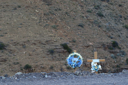 Flowers and crosses mark the spot for victims of a fatal vehicle accident