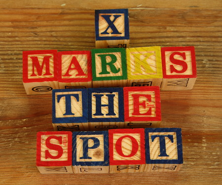 x marks the spot: The term X marks the spot visually displayed using colorful wooden blocks
