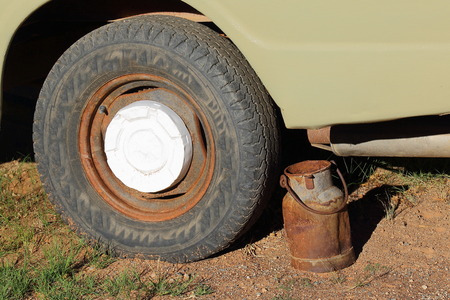 days gone by: A rusted old milk can next to the wheel of an old abandoned vehicle