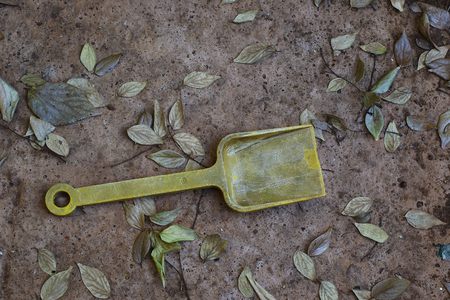 days gone by: An abandoned and faded yellow childs toy spade Stock Photo