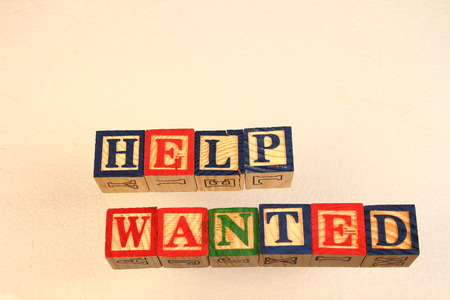 The term help wanted visually displayed using colorful wooden toy blocks Stock Photo