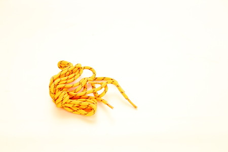 Colorful yellow boot laces on a white background in landscape format with copy space