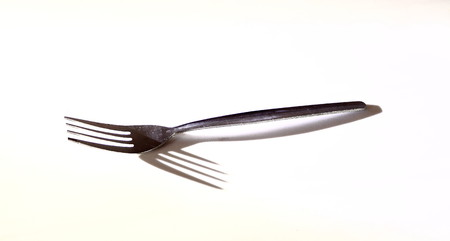 contradict: Silver fork with shadows of the prongs facing in the opposite direction on a white background in landscape format with copy space