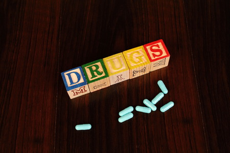 The term drugs displayed visually using colorful wooden blocks together with blue capsules on a dark background in landscape format with copy space Stock Photo