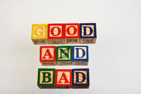 format: The term good and bad displayed visually using colorful wooden blocks on a white surface in landscape format