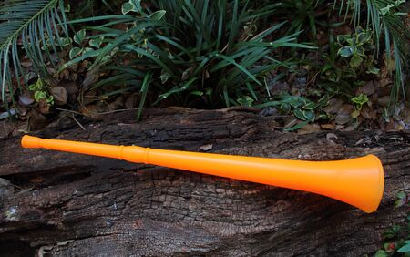 Orange colored vuvuzela - a plastic horn instrument that produces a loud monotone note used at football matches in Africa Stock Photo