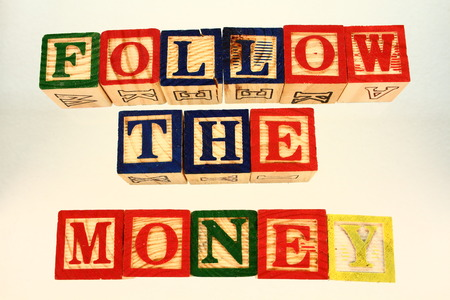 illustrates: The term follow the money visually displayed on a white background using colorful wooden blocks in landscape format with copy space Stock Photo