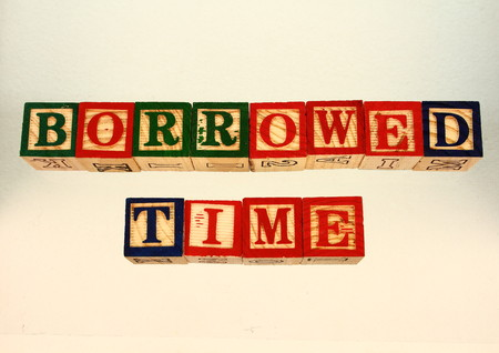 borrowed: The term borrowed time visually displayed on a white background using colorful wooden blocks in landscape format with copy space