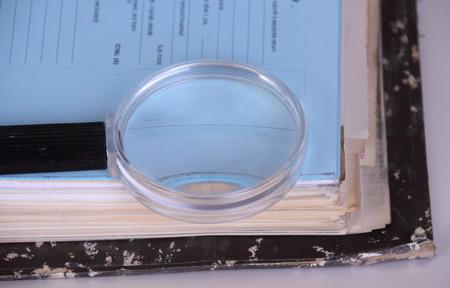 Fichier avec des documents et une loupe sur un fond blanc avec espace de copie Banque d'images - 81705278