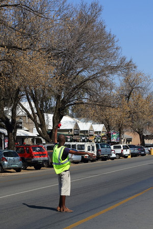 Parys, South Africa - unempolyed man operates as a freelance paring attendant to assist motorists to find parking to generate income from tips