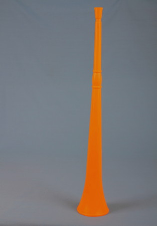Orange colored vuvuzela or plastic horn against a clear background in portrait format with copy space