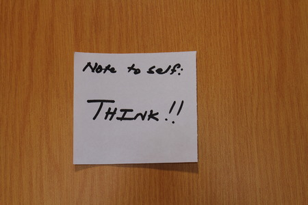 Note with the motivational message think written on it and stuck to a notice board in landscape format with a clear background and copy space Stock Photo
