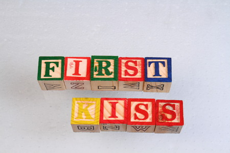 jargon: The term first kiss displayed visually on a white background using colorful wooden toy blocks in landscape format with copy space