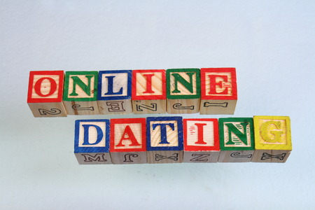 The term online dating visually displayed on a white background using colorful wooden toy blocks in landscape format with copy space