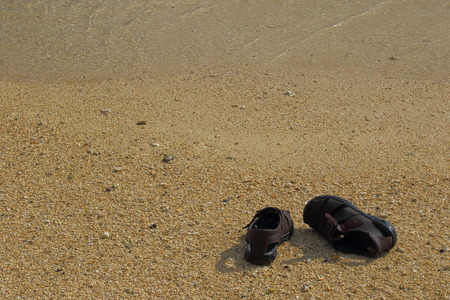A pair of abandoned brown leather sandals on a deserted beach in landscape format with copy space Stock Photo