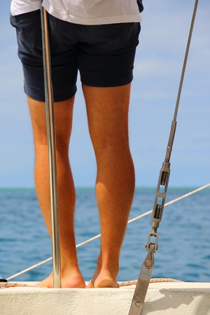 View of sun tanned human legs from behind o a yacht with a tropical island background in portrait format with copy space